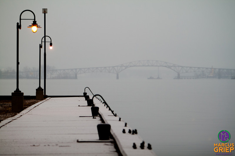Two lampposts add an eerie effect in the fog on the Port Henry dock in front of the Champlain Bridge. The dock was at one time used to load barges with iron-ore with a short, narrow gauge railroad bringing the ore to be loaded onto the ships.