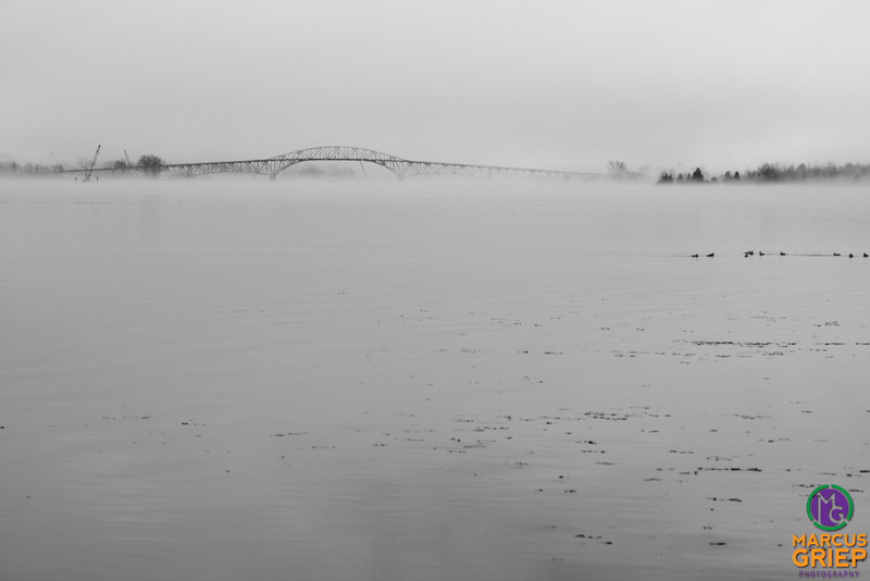 Bits of ice float around Bulwagga Bay in Lake Champlain next to the Champlain Bridge as crews work to place explosive charges under the cover of fog while ducks play nearby.