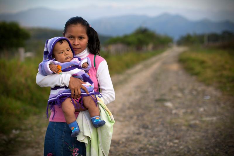 Camino a la escuela una joven lleva su bebé a la clase.