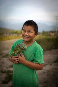 El hijo de Dora y Henry posa con su loro.