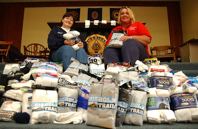 Carol Knapp, left, president of American Legion Auxiliary Post 12, and Johni Wressell,  1st vice-president, sit among sock donations for the homeless, donated by Vermilion AMVETS Post 22, Oct. 13.   Steve Manheim