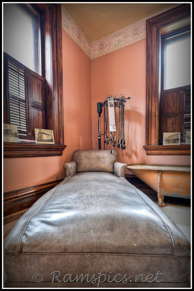 """I'm told this is an antique """"fainting chaise""""  on display at the Courthouse Square Museum, in Charlotte Michigan.<br /> <br /> Should you feel the need to refresh after """"fainting"""" a claw foot tub is available as are (rack in corner) electric hair curlers (with cords) from the early 1900's... the chaise is one of many unique artifacts at the museum."""