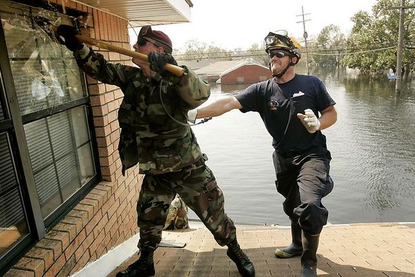 9/10/05 -- New Orleans, LA --  Tim O'Malley, a firefighter with the California Task Force 8, right cq, assists Sean Matthews of the 82nd Airborne Division 3rd Platoon Charlie Company 307 Engineer Batallion in busting in an attic window as part of a search, rescue and recovery mission in the severely flooded 3rd precinct of New Orleans on Saturday, September 10, 2005. Boston Globe Photo - reproduction requires explicit written permission from the Boston Globe.