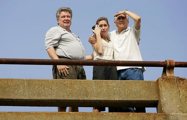 9/5/05 -- Jefferson Parish, Louisiana -- Lisa and Warren Dauzat (left and middle)  break into sobs as they catch view of their business, which had been flooded by Hurricane Katrina and then ravaged by looters. On the right is their employee, Roberto Angeli. CQ all. The business is called Precision-Greiner Equipment, which sells automotive supplies. They are standing on South Causeway Boulevard at the overpass of Airline Highway in Jefferson Parish. Thousands of residents streamed back to Jefferson Parish starting at dawn on Monday morning, September 5, 2005 to encounter a range of property losses. Some found flooded and looted properties and businesses, some encountered total loss, other were pleasantly surprised at how well their properties weathered Hurricane Katrina. Cars were backed up for miles leading into Jefferson Parish on Airline Highway. Many  of the vehicles were driven by passengers who slept in their cars overnight to secure a spot in line. People were required to show proof of residence in order to pass police check points. Boston Globe Photo - reproduction requires explicit written permission from the Boston Globe. Story by Stephen Smith, Boston Globe Staff.