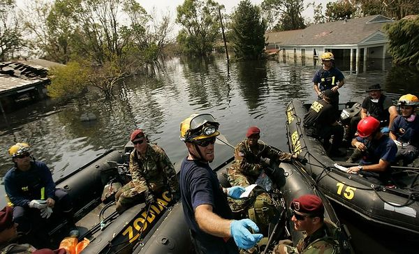 9/10/05 -- New Orleans, LA --  Tim O'Malley, a firefighter with the California Task Force 8, gives orders to members of the 82nd Airborne Division 3rd Platoon Charlie Company 307 Engineer Batallion, who conducted search, rescue and recovery missions aboard Zodiac boats in the severely flooded 3rd precinct of New Orleans on Saturday, September 10, 2005. Boston Globe Photo - reproduction requires explicit written permission from the Boston Globe.