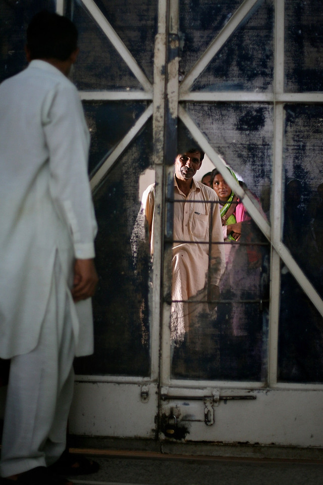 """USAID funded faith-based aid abroad"" - August 29, 2006 - Sehiwal, Pakistan -  Sehiwal District Hospital - People wait in the crowded hallways outside a ward but peer through the hole in the door at the people inside. This is an example of the decrepit state of the district hospital. Many of the screens are riddled with holes, and all the exteriors are in need of maintenance. There are two hospitals in the city of Sehiwal, Pakistan, a city of 200,000. One is the USAID and privately-funded Christian hospital that sees roughly 14,000 patients per year. The other is the Pakistani Government-run hospital that sees  nearly one million patients per year, both in-patient and out-patient. It is drastically underfunded and lacks proper building maintenance or the staff to maintain sanitary conditions. The hallways overflow with sick patients and concerned family, and the staff is limited and over-taxed. By contrast, the Christian hospital is gleaming, sanitary, and well funded. In fact, it has advanced equipment that it cannot even use for lack of technicians. The hospital runs far below capacity, and the nurses repeatedly check patients' vitals for lack of other tasks. Boston Globe Photo - no reproduction without explicit written permission from the Boston Globe."