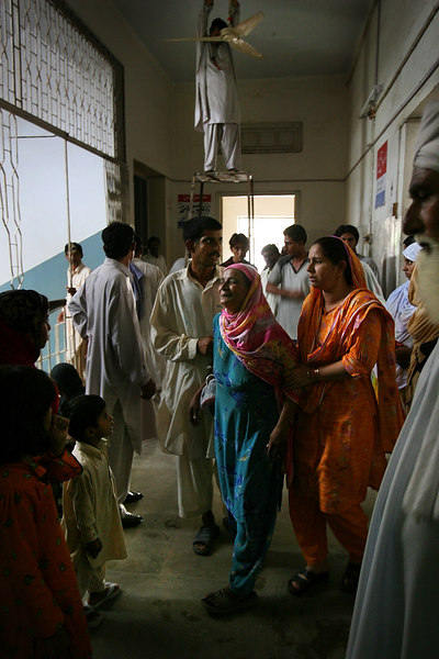 """USAID funded faith-based aid abroad"" - August 29, 2006 - Sehiwal, Pakistan -  Sehiwal District Hospital - A woman paces the over-crowded hallways of the Sehiwal District Hospital wailing, ""My son! My son! He's died! I've lost my son! I'm now alone! Listen! My child is dead!"" A hospital worker stands behind her making repairs to a ceiling fan.   There are two hospitals in the city of Sehiwal, Pakistan, a city of 200,000. One is the USAID and privately-funded Christian hospital that sees roughly 14,000 patients per year. The other is the Pakistani Government-run hospital that sees  nearly one million patients per year, both in-patient and out-patient. It is drastically underfunded and lacks proper building maintenance or the staff to maintain sanitary conditions. The hallways overflow with sick patients and concerned family, and the staff is limited and over-taxed. By contrast, the Christian hospital is gleaming, sanitary, and well funded. In fact, it has advanced equipment that it cannot even use for lack of technicians. The hospital runs far below capacity, and the nurses repeatedly check patients' vitals for lack of other tasks. Boston Globe Photo - no reproduction without explicit written permission from the Boston Globe."