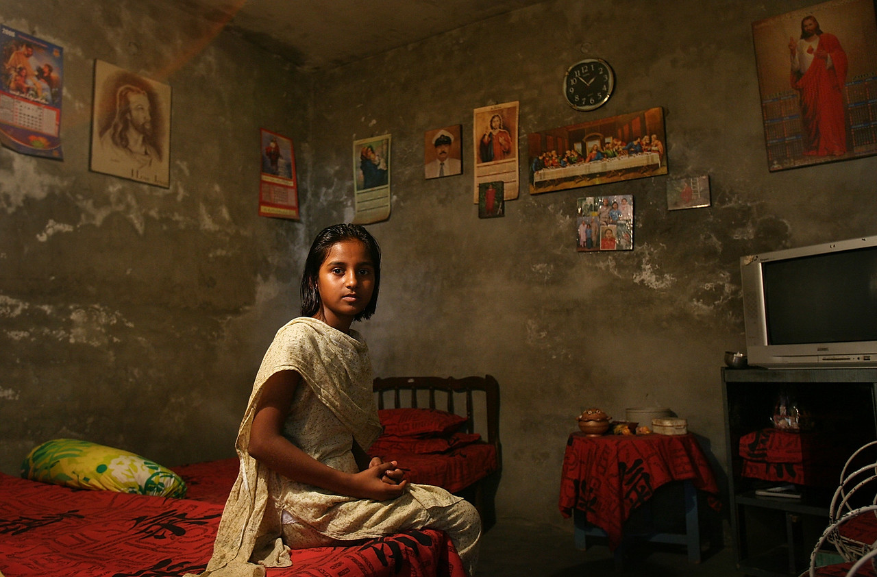 "8/26/2006 - This is a portrait of Nida Youssaf, cq, 12, in her room in Sheikhupura, Pakistan. She has religious pictures on her wall, she says, ""because I love Jesus.""  The Christians of Pakistan are generally very poor.  These are photographs from the mixed Christian/Muslim community outside of Lahore, Pakistan called Sheikhupura.  on August 26, 2006. ""USAID funded faith-based aid abroad"" - Pakistan -  Boston Globe Photo - no reproduction without explicit written permission from the Boston Globe."