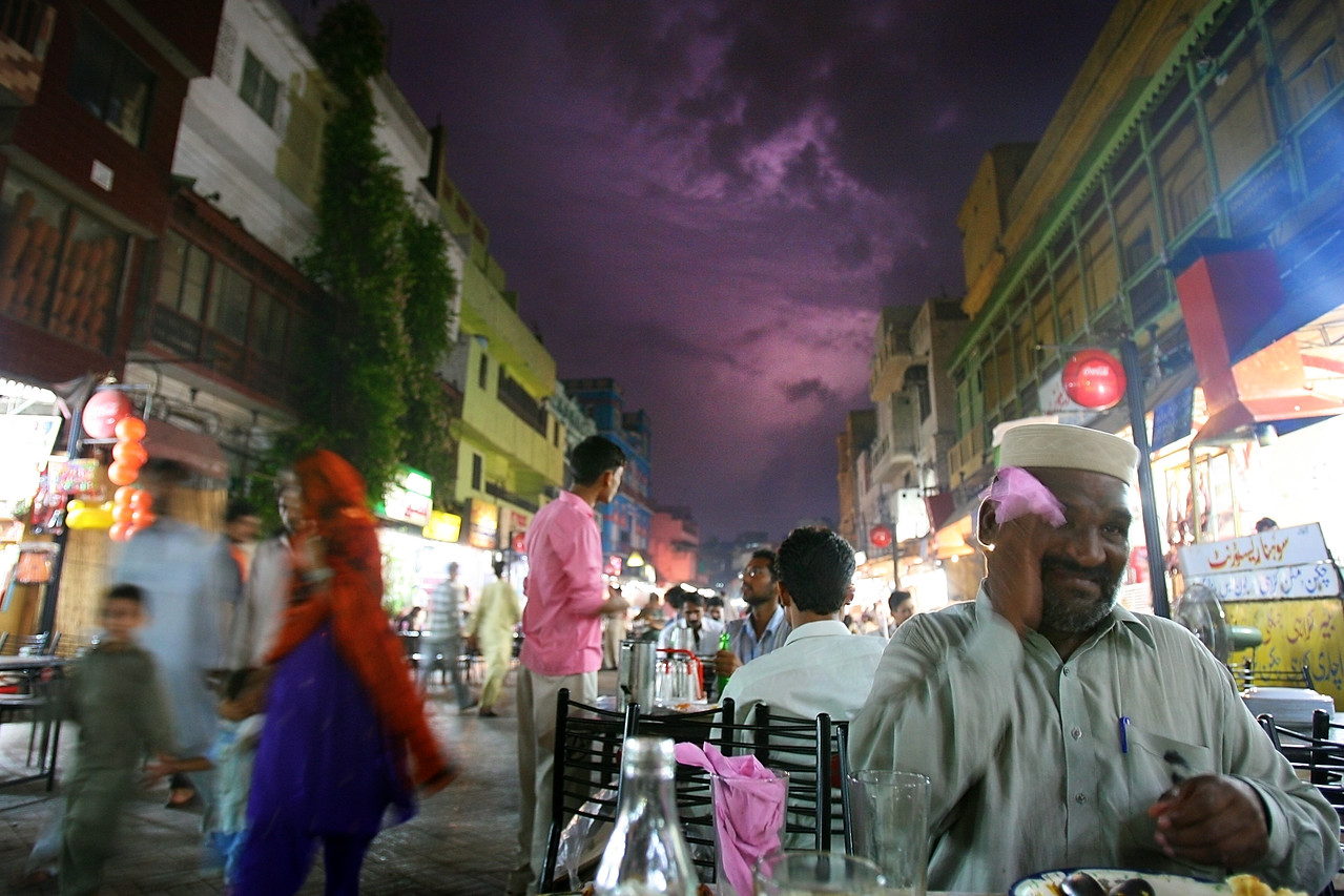 "8/27/2006 - Lahore, Pakistan - These are scenes from Food Street, a famous stretch of road in Lahore, Pakistan known for its bustling scene and numerous food vendors. A lightning storm lit up the sky at dusk and then opened up to a fierce monsoon.   ""USAID funded faith-based aid abroad"" - Pakistan -  Boston Globe Photo - no reproduction without explicit written permission from the Boston Globe."