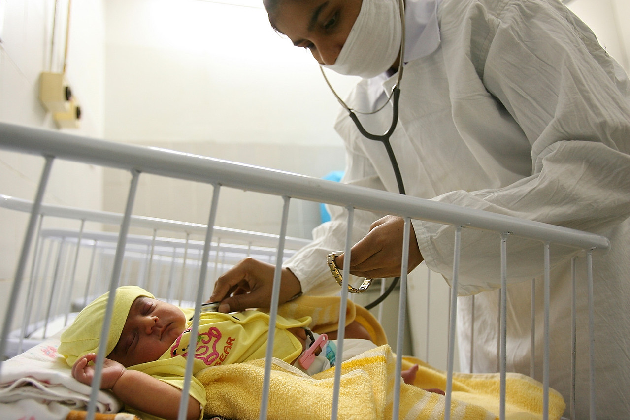 """USAID funded faith-based aid abroad"" - Sehiwal, Pakistan -  Sehiwal Christian Hospital - A uniformed nurse attends to a healthy newborn in the sparkling clean neonatal unit at the Sehiwal Christian Hospital. There are two hospitals in the city of Sehiwal, Pakistan, a city of 200,000. One is the USAID and privately-funded Christian hospital that sees roughly 14,000 patients per year. The other is the Pakistani Government-run hospital that sees  nearly one million patients per year, both in-patient and out-patient. It is drastically underfunded and lacks proper building maintenance or the staff to maintain sanitary conditions. The hallways overflow with sick patients and concerned family, and the staff is limited and over-taxed. By contrast, the Christian hospital is gleaming, sanitary, and well funded. In fact, it has advanced equipment that it cannot even use for lack of technicians. The hospital runs far below capacity, and the nurses repeatedly check patients' vitals for lack of other tasks. Boston Globe Photo - no reproduction without explicit written permission from the Boston Globe."