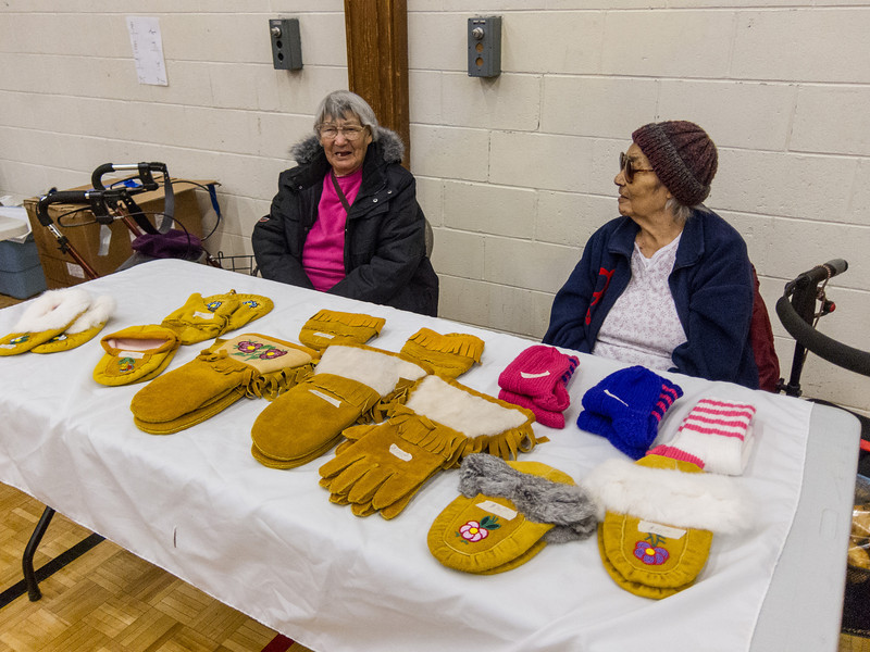 Christmas Bazaar at James Bay Education Centre in Moosonee.- Sabeth Kaysook and Lottie Paulmartin selling handmade moose hide and woolen handicrafts.