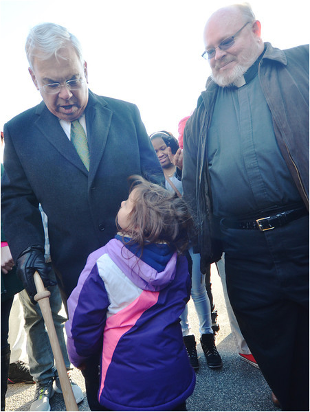 Anastajia Balbuena, a 4 year-old neighborhood resident, greets Mayor Menino. At right is the pastor of the Dorchester Tri-Parish, Father Jack Ahern.