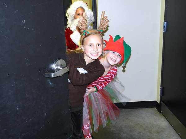 "Tony Goetz Elementary School third-graders from left, Santa, Lucas Newton; reindeer, Piper Mathews; and elf, Grace Lynch, peek around the door as they wait for their parts in ""Christmas at the O.K. Corral, A Rootin' Tootin' Musical."""
