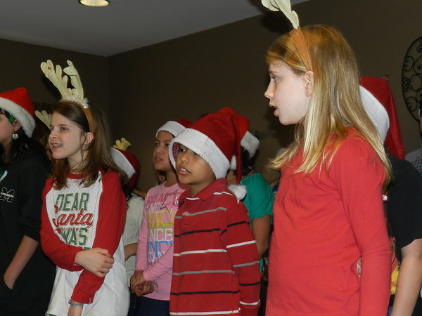 Irving Elementary School singers Kathryn Willis, left, Brayan Barbosa and Kynzi Willis perform at Country Gardens Assisted Living Center. The performance, their fourth on Friday, was part of the choir's winter concert tour.