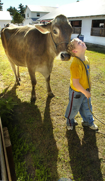 Cody Mills, 9 who lives in Rockwood  on Pittston Farm waits for a wash bay to open up at the Fryeburg Fair.  He was helping his aunt from Silver Shade Farm in New Sharon get her cows ready for showing.