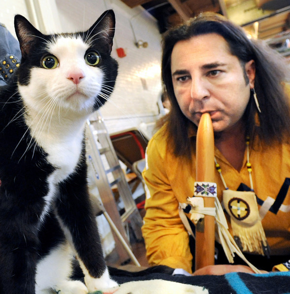 Cat whisperer Michael Redsky plays a tune on his flute for Rupert, a 4 year old cat belonging to Donna Madison of Portland at the Cat Show at the Lewiston Armory.