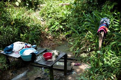 La comunidad tampoco tiene servicio de agua potable. No ha llovido en un mes y las mujeres lavan la ropa en una quebrada de aguas estancadas y contaminadas.