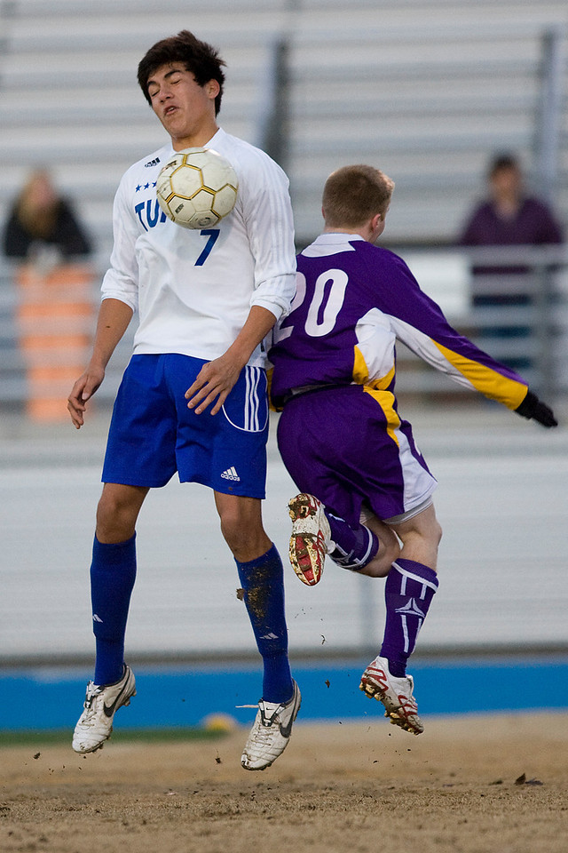 Tupelo's Junior Garcia beats Desoto Central defender Tanner Moore to the ball near midfield