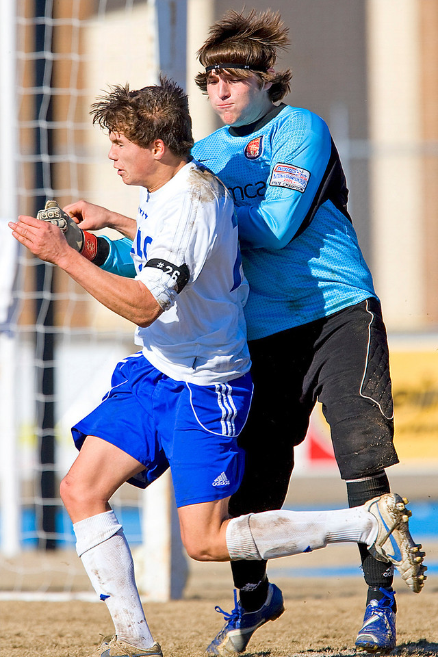 Tupelo's Jake Heyer colides with Clinton goalie DJ Marble after scoring the winning goal