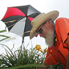 """20JUL11  Tommy Nash, an employee of the Avon Parks was attending to some landscaping in that town, keeps the heat beat by """"Drinking lots of water and Gatorade.""""  He also sets up the umbrella by spiking it into the ground and wears a white, solar reflecting hat.  photo by Chuck Humel"""