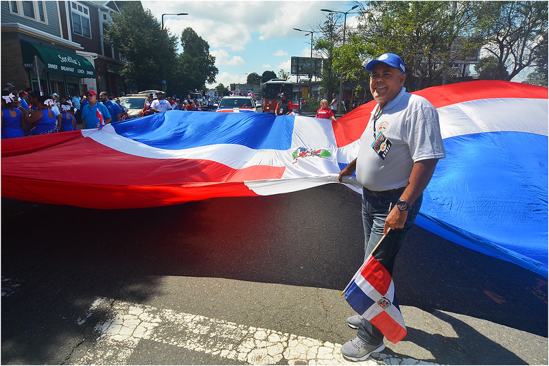 Parade Director Alexis Troncoso with Dominican flag near Hyde Square.