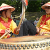 Joey Thach (left) tries beating a traditional war drum as Trinh Hoang looks on in the Vietnamese Traditional Martial Arts float.