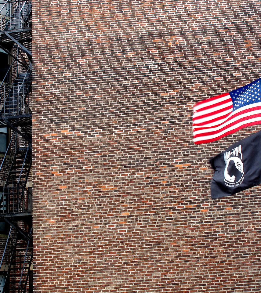 "Engine Company 37 Ladder 26<br /> Roxbury<br /> <br /> Armed with a basic narrative of fire escape history in America, and already fully engaged in photographing Boston's varieties, a thought occurred to me ….. What does the Fire Department think about this mode of burning building escape? And, if I could present my portfolio-in-progress to the Chief at nearby Roxbury's Engine Company 37 Ladder 26, in addition to learning the Department's views, maybe I could parlay a chance to expand my shooting vantage point repertoire with images from the station's training ladders! <br /> <br /> Despite the proximity of what I considered a convenient ""practice"" building shown here adjacent to the station, I was in for surprising answers. Forget private buildings, no matter how conveniently close. There's a special, designated training site in Quincy, complete with building mock ups, where new recruits attend fire ""Boot Camp."" And forget ladders; the ""Bucket"" on a crane-like truck attachment is the preferred rescue method. <br /> <br /> Firemen actually disdain use of fire escapes. Whoa, that was news! Unfortunately the safety value of the fire escape I visually admired has gradually been denigrated due to periodic inspections and required maintenance procedures that were MIA. Throw function not following form into the mix and tragic outcomes can occur.  It happened in Boston in 1975 and contributed to changes in how this urban escape art is perceived. Stay tuned……..<br /> <br /> By the way, I did get an invitation to Quincy to photograph from the ""Bucket."""