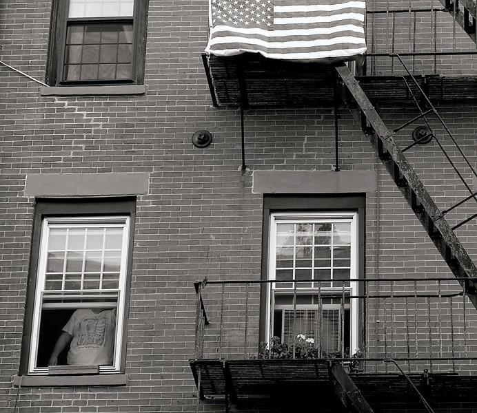 "America the Beautiful<br /> North End, Boston<br /> <br /> Robert Frank's documentary work is well known to generations of street photographers striving to emulate his gritty style. In The Americans, his signature 1950's work based on a road trip criss-crossing his adopted country, our Stars and Stripes is present in each image introducing a new section. My own North End neighborhood image, with a shadowy window figure, resembles his original cover photo taken from a passing parade in Hoboken, NJ. Despite Frank's current recognition, at first his work was not universally adulated. <br /> <br /> Having recently arrived in the US from his native Switzerland, and fueled with a Guggenheim Fellowship acquired through the influence of Walker Evans, scion of the New Deal Era photography, Robert Frank traveled the US more than a half century ago recording the America he encountered on 35 mm film. Two years, 800 rolls with almost 30,000 negatives later, the journey morphed into an arduous editing phase. That ultimately yielded only 80 photographs! In the pre-publication maquette these were grouped into four sections sequenced with images, all untitled, strategically positioned for added impact on opposing pages. Frank's Bohemian good buddy Jack Kerouac, already known for his literary prowess, wrote a priceless introduction (which is a must read) to complete the final piece of the impressive photo-documentary. How perfect! <br /> Trouble was, it was panned by critics and shunned by publishers. It seemed the mirror held up to our nation by The Americans did not coincide with the ""Fairest in the Land"" reflected image the country wanted to see. <br /> <br /> Still in the 1950s glow of post-war euphoria, the US was not in the mood to confront residual harsh realities of segregation, a deep Have and Have-not chasm, political demagoguery, and the darkening clouds of the ensuing Cold War portrayed in Frank's photos. The Americans did eventually get a publisher, but in France! This past year the Museum of Modern Art featured a major retrospective of The Americans. The final image is one of the photographer's exhausted wife and child asleep inside an old Ford on the side of a long, lonely road at dawn. It is a fitting metaphor for Frank's two year odyssey.<br /> <br />  The Americans was to be Frank's last photo-essay."