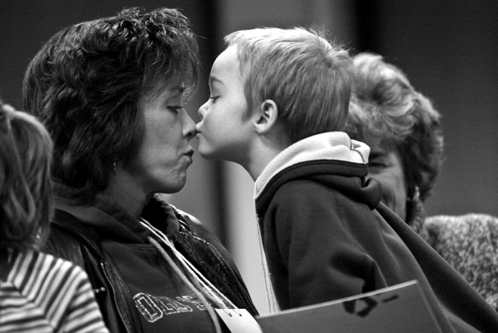 Adam kisses his mother Lesa on the nose during a quiet moment before the first night of the seven week grief support group. Behind Adam sat his Aunt Candace who attends the group with them.