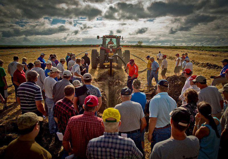 A group of farmers watched a tiling demo at the Hefty Brother's Ag-PHD Field Day on Friday, July 27, 2012, in Baltic, South Dakota. At the Ag-PHD Field Day farmers come from the surrounding states to learn how to pick the right herbicides, how to better fertilize crops and other farming techniques such as tiling a field. The ease of tiling has made many lands such as wetlands and prairies easier and profitable to farm and threatening South Dakotas remaining native prairies.
