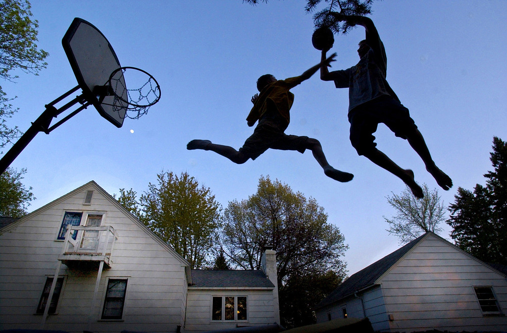 Paul Hammitt and his brother Phill play basketball while jumping on a trampoline in their backyard on May 12, 2003 at dusk in Owatonna, Minn.