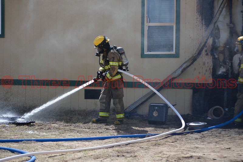 A firefighter extinguishing flames on debris from a structure fire in Ellicott, Colorado. April 8, 2015