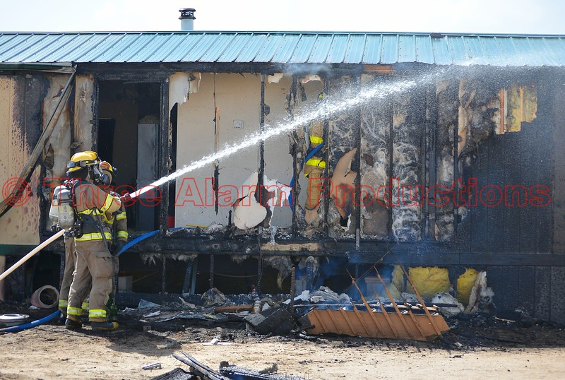 Firefighters extinguishing hot spots on a mobile home fire in Ellicott, Colorado. April 8, 2015