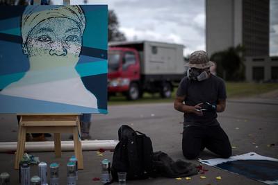 """El grafitero DjLu realizando una obra por la memoria de los desaparecidos. """"Usa tu cabeza""""."""