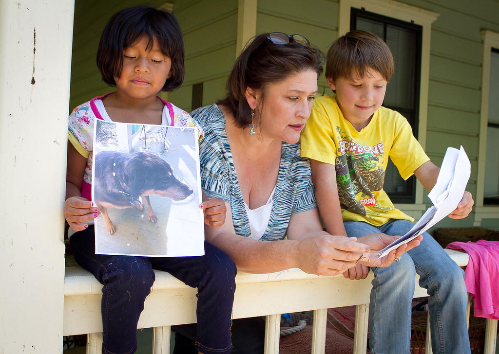 Erika Gregory with her children, Jack and Lucy Mollner at their home in Vallejo, Calif., on Thursday, May 17th, 2012. Lucy holds up a picture of  their dog Belle who was shot by a police officer when the officer came to their home to take afraid report.