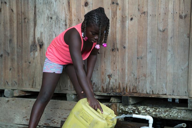 """Mujeres, hombres, niñas y niños aparecen con sus """"galonetas"""" (bidones) vacías, en los tres o cuatro puntos de recogida de agua que hay en la calle, y mientras esperan con paciencia su turno para llenarlas, charlan y ríen. Algunas de las mangueras que proveen el agua se encuentran bajo las casas, y la gente debe meterse entre el barro y la basura para llenar las galonetas."""