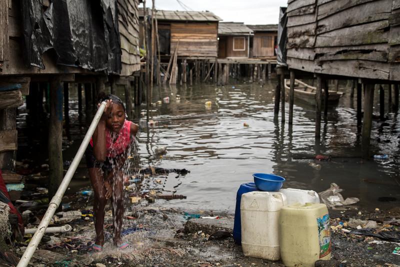 Una niña aprovecha el agua, que llega cada tres días, para ducharse.