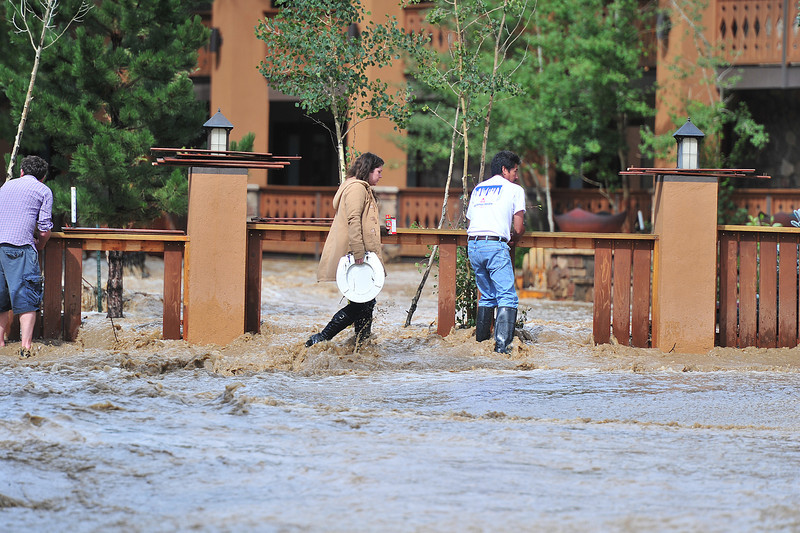 Peopl carry what they can from businesses on West Elkhorn Avenue as the Fall River covers the west end of downtown Estes Park.