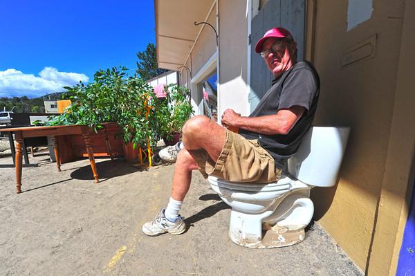 Dave Boon, owner of the building housing Range Realty and the Estes Angler, takes a break after removing items from the offices. Estes Park is drying out and cleaning up a week after the rain and floods began.