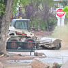 A town bobcat sweeps mud off of Elkhorn Avenue on Sunday. The town has started cleaning where they can.