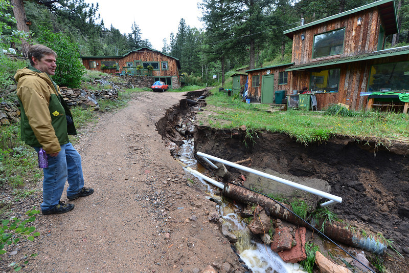 Frank Crone of Glen Haven surveys damage to his property on Monday. Crone counts himself among the lucky as he had electricty and running water when he returned to his home after the flood.
