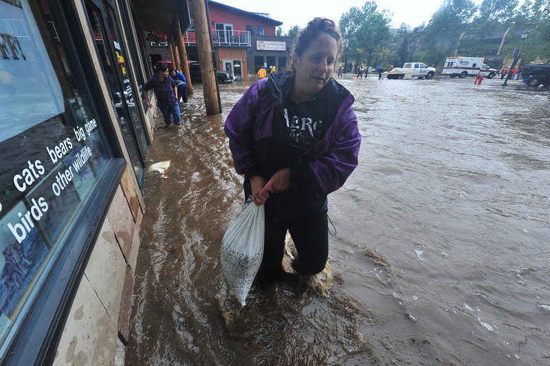 Volunteers slog through dirty water to place sandbags along east Elkhorn Avenue on Thursday night.