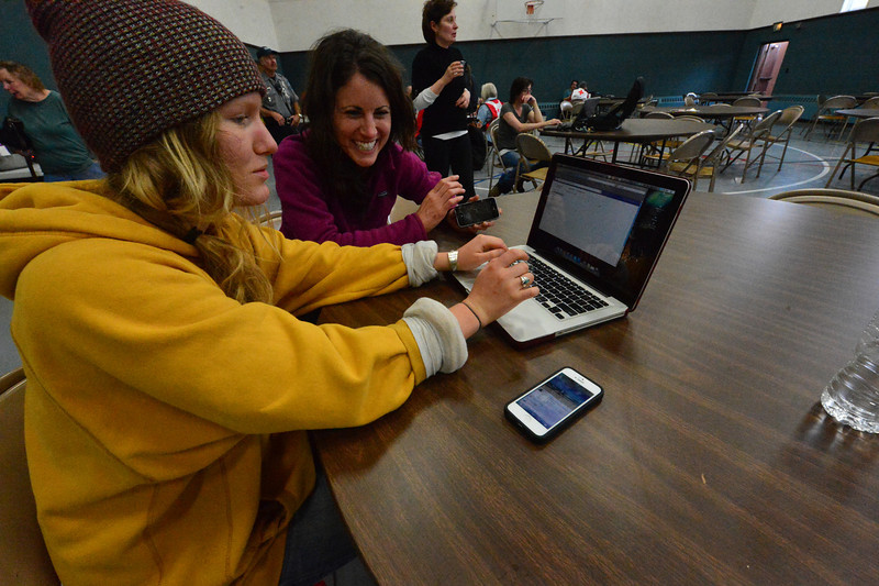 Annie Stewart, left, of Denver e-mails her parents while Vanessa O'Neal of Olive Springs, Tenn., cheerfully waits her turn at the Mountain View Bible Fellowship on Friday. The evecuation center at the church provided a connection to the outside world for those stuck in Estes Park.