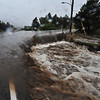 The Fish Creek runs over its namesake road at Brodie Avenue on Thursday morning. Waters rose trapping residents in their neighborhoods as rain continued.