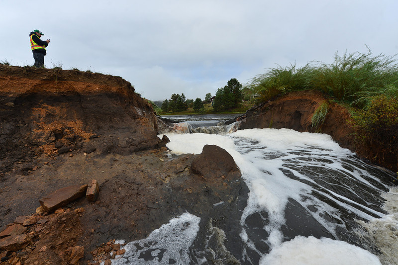 An Estes Park Public Works official documents the breach in the lower Scott Pond on Friday morning. The dam failure added more water to the already overflowing Fish Creek.