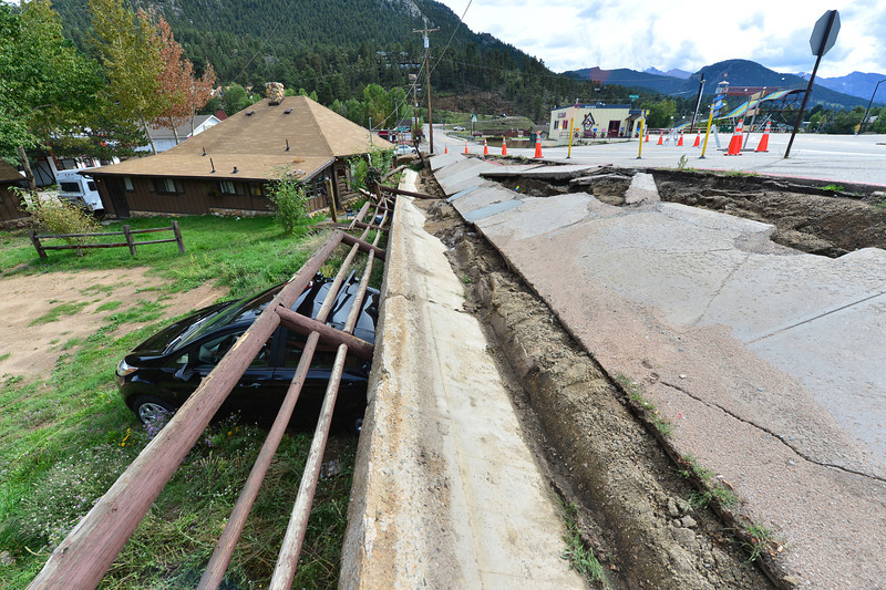 Saturated soil collapses, bring a retaining wall down atop a parked car below Morain and Crags avenues on Friday. Saturated soil has washed away all over Estes Park.