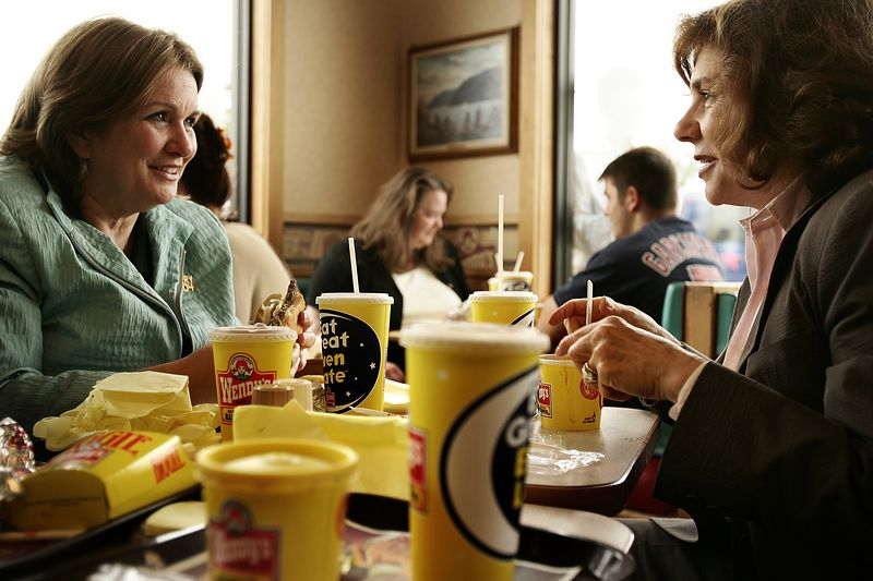 7/30/2004 -- Newburgh, NY -- Wendy's Fast Food Restaurant -- Senators John Kerry and John Edwards and their wives, Teresa and Elizabeth, stopped at a Wendy's in Newburgh, NY as a nod to the Edwards' annual tradition of dining at Wendy's on their wedding anniversary. Kerry is on a cross-country campaign tour which will take him as far west as Oregon via bus, train and boat. In this picture, Elizabeth Edwards (left) and Teresa Heinz Kerry talk at the table before their husbands arrive to join them.  Photo by Dina Rudick, Boston Globe staff.