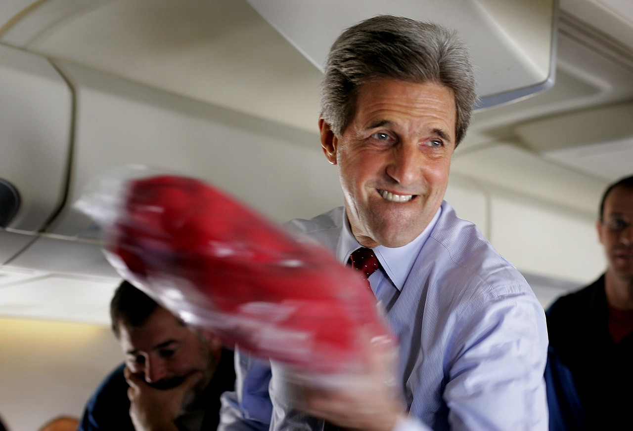 """11/2/2004 -- On Kerry campaign airplane from La Crosse, WI to Boston, MA -- Senator John Kerry distributes polartech fleece pull-overs with the words """"Kerry Edwards The Real Deal Express Press Corps"""" embroidered on them while flying from Wisconsin to Massachusetts on voting day, November 2, 2004. Photo by Dina Rudick, Boston Globe Staff"""