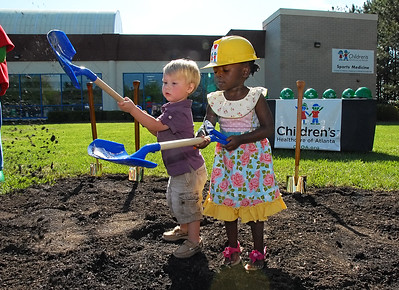 04-18-13  --choa imaging center 02--  From left, Collier, 2, and Emmy Lott, 3, have fun with the dirt during Thursday morning's groundbreaking of the Pediatric Imaging Center at Children's Healthcare of Atlanta at Town Center.  Collier has epilepsy and his sister Emmy has sickle cell anemia and they are both patients of Children's Healthcare of Atlanta.  STAFF/LAURA MOON.