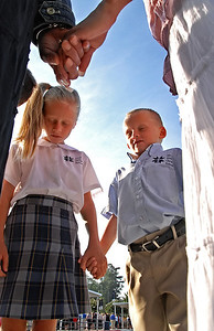 08-21-12  --nccs circle of prayer 01--  Fourth grader Molly Wooldridge, 9, and her brother Blake Wooldridge, 6, gather in a small circle to pray during the Circle of Prayer event at North Cobb Christian School on Tuesday morning.  STAFF/LAURA MOON.